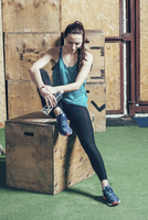 Full length of female athlete holding water bottle while sitting on wooden box at gym