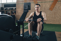 Determined man exercising on rowing machines at gym 11016035144| 写真素材・ストックフォト・画像・イラスト素材|アマナイメージズ