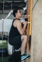 Side view of male athlete climbing wall at gym