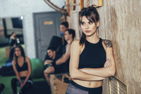 Thoughtful female athlete standing arms crossed with friends in background at health club