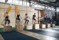 Full length of determined athletes doing box jumping at gym