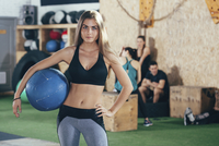 Portrait of confident sportswoman holding fitness ball at health club