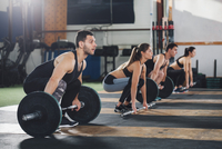 Dedicated male and female athletes lifting barbells at gym