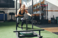 Determined woman doing sled push exercise at health club