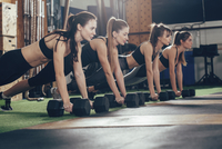 Determined athletes doing push-ups on dumbbells at health club