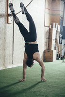 Rear view of sportsman doing handstand in gym