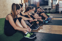 Male and female athletes talking while sitting on carpet at gym