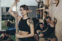 Portrait of confident female athlete holding rope while standing at gym with friends in background