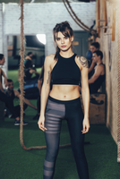 Portrait of confident sportswoman standing at gym with friends in background