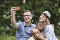 A couple with their Shar-pei/Staffordshire Terrier dog at the park taking a selfie