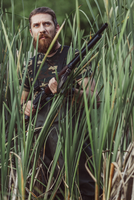 Hunter looking away while standing on grassy field