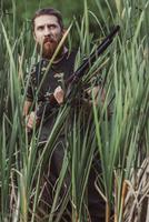 Hunter looking away while standing on grassy field 11016035177| 写真素材・ストックフォト・画像・イラスト素材|アマナイメージズ