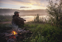 Side view of hunter sitting by bonfire on field at lakeshore during sunset 11016035178| 写真素材・ストックフォト・画像・イラスト素材|アマナイメージズ