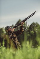 Hunter aiming rifle on field against sky