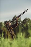 Hunter aiming rifle on field against sky 11016035179| 写真素材・ストックフォト・画像・イラスト素材|アマナイメージズ