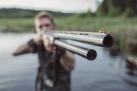 Hunter aiming rifle while standing at lakeshore