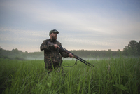 Hunter holding rifle while standing on field against sky