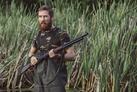Hunter holding rifle while looking away on grassy field