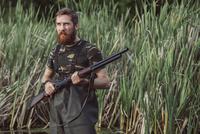 Hunter holding rifle while looking away on grassy field 11016035186| 写真素材・ストックフォト・画像・イラスト素材|アマナイメージズ