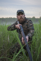 Hunter holding rifle while looking away on field