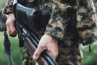 Midsection of hunter holding rifle