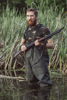 Hunter holding rifle standing in lake by grassy field