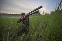 Hunter aiming rifle while kneeling on field against sky 11016035190| 写真素材・ストックフォト・画像・イラスト素材|アマナイメージズ