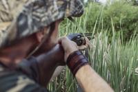 Rear view of hunter aiming rifle on field 11016035192| 写真素材・ストックフォト・画像・イラスト素材|アマナイメージズ