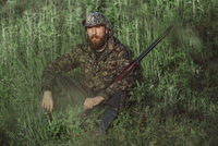 Hunter holding rifle while sitting on grassy field