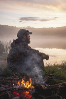 Side view of hunter sitting by bonfire at lakeshore during sunset 11016035195| 写真素材・ストックフォト・画像・イラスト素材|アマナイメージズ