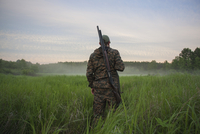 Rear view of hunter standing at grassy field 11016035196| 写真素材・ストックフォト・画像・イラスト素材|アマナイメージズ