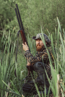 Hunter holding rifle while sitting on field