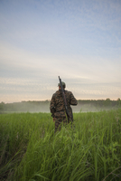 Rear view of hunter standing at grassy field against sky