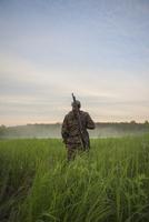 Rear view of hunter standing at grassy field against sky 11016035200| 写真素材・ストックフォト・画像・イラスト素材|アマナイメージズ