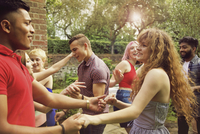 Cheerful friends dancing at yard during party