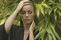 Close-up of sensuous woman with hand on head by plants at yard