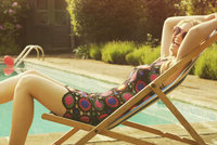 Side view portrait of cheerful woman relaxing on deck chair at poolside 11016035222| 写真素材・ストックフォト・画像・イラスト素材|アマナイメージズ
