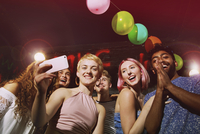 Low angle portrait of happy woman taking selfie with friends at yard