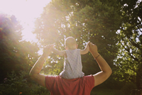 Rear view of father carrying baby boy on shoulders at yard during sunny day