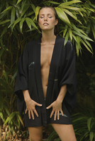 Sensuous woman in bathrobe standing with eyes closed against plants at yard