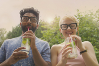 Low angle view of cheerful couple drinking lemonade at yard