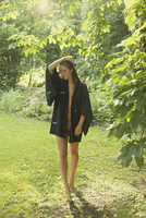 Sensuous woman in bathrobe walking at yard