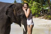 Portrait of smiling woman embracing elephant on sea shore