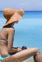 Side view of woman wearing bikini sitting by sea on sunny day