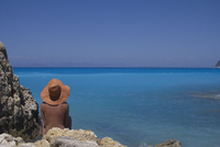 Rear view of woman relaxing on rocky sea shore against clear blue sky