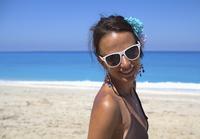 Beautiful woman smiling and wearing sunglasses at beach