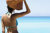 Woman wearing bikini and holding sun hat while standing on beach