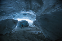 A man carrying snowboard while walking in ice cave, Whistler, British Columbia, Canada