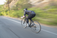 Blurred motion view of man cycling on country road