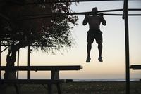 Full length of man doing chin-ups at park against sky at sunset